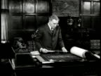 John D Rockefeller Jr standing at desk flipping through blueprints holding ruler measuring blueprints MS Rockefeller Philanthropist New York City NYC