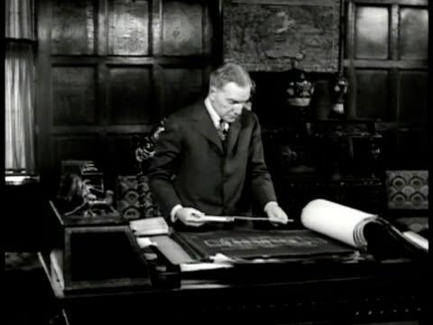 John D Rockefeller Jr standing at desk flipping through blueprints holding ruler measuring blueprints MS Rockefeller Philanthropist New York City NYC