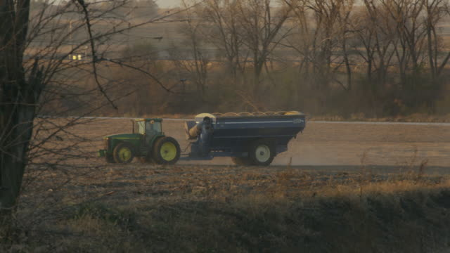 John Deere tractor pulls a grain wagon back into the field for another load of soybeans during harvest.