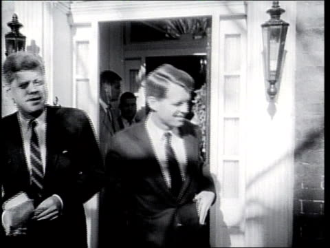 John F Kennedy and Robert F Kennedy stand in front of John's house talking to reporters