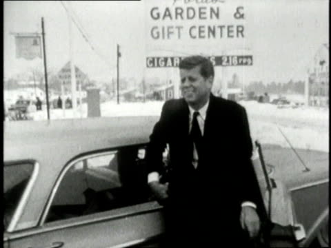 John F Kennedy exiting a car and shaking hands with people / United States