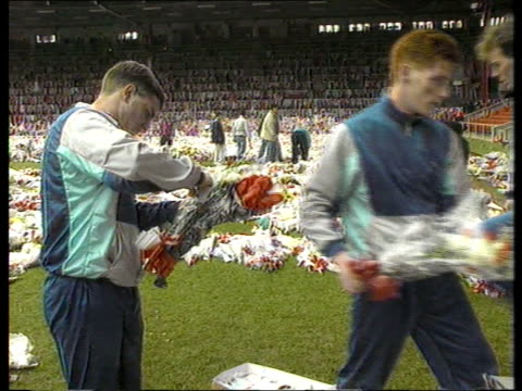 John Paul Gilhooley funeral Liverpool Anfield TGV Flowers covering pitch PULL OUT mass of flowers MS Footballers from Tranmere Rovers clearing...