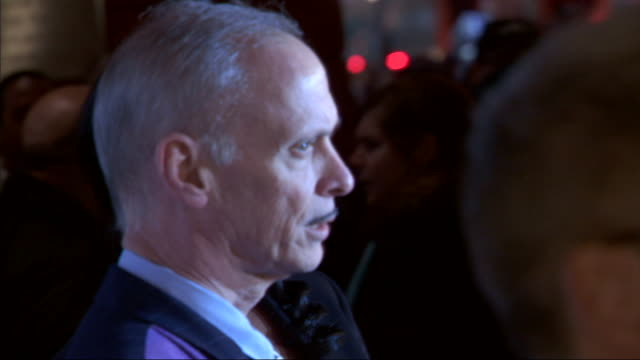 MS John Waters and Sharice Waters moving along the red carpet posing for the paparazzi at the Stephen Sondheim Theater