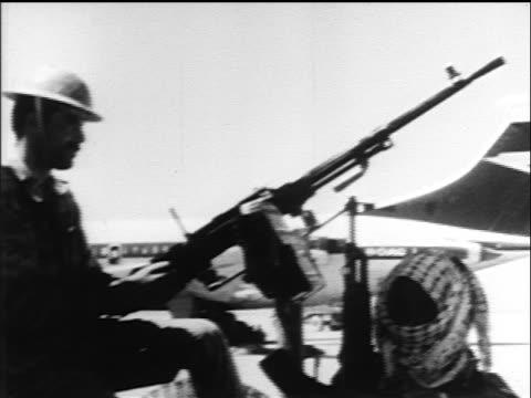 Jordanian soldier sitting at gun with hijacked airliner in background / PLO hijacking / Jordan