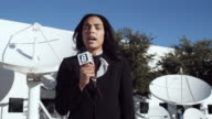 MS DS Journalist talking into microphone in front of satellite dishes, Dallas, Texas, USA
