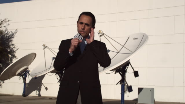 MS Journalist talking into microphone in front of satellite dishes, Dallas, Texas, USA