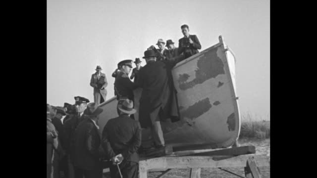 VS journalists policemen and civilian men and women examine a lifeboat from the damaged ship SS Morro Castle the lifeboat sits on a beach groups walk...
