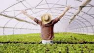 DS vreugdevolle tuinman outstretching zijn armen omhoog in de kas