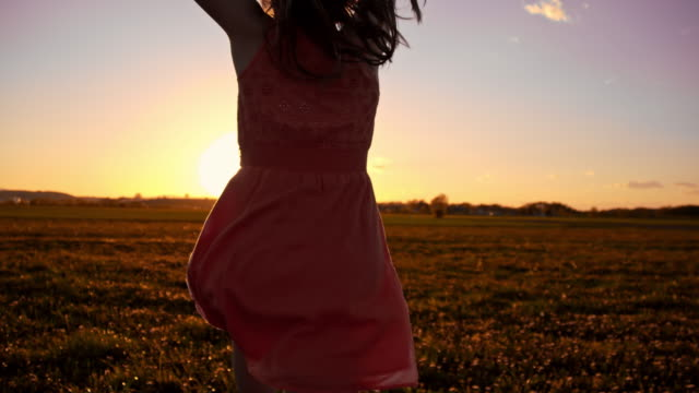 SLO MO Joyful girl in the meadow at sunset