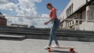 Joyful girl riding skateboard