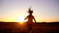 SLO MO Joyful girl running in grass at sunset