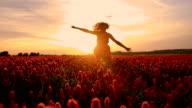 SLO MO Joyful girl running in the field of flowers