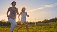 SLO MO fröhlich Mutter und Tochter auf Gras Laufen
