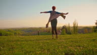 SLO MO Joyful woman spinning in meadow