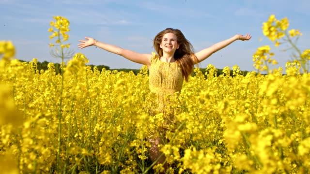 SLO MO Joyful young woman running among blooming canola