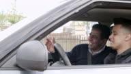 Joyous father teaching teen to drive car