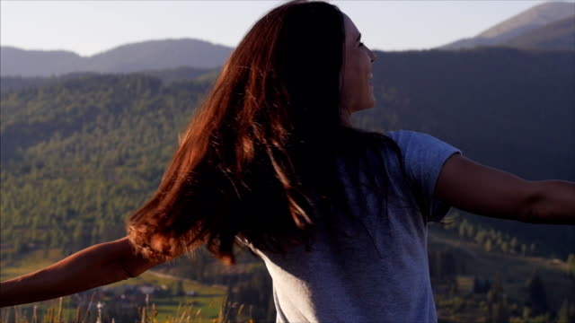 Joyous woman whirling at sunset in mountains