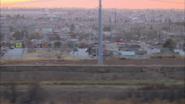 LOW AERIAL Juarez, Mexico and 'border wall' of US-Mexican border at El Paso, Texas, USA