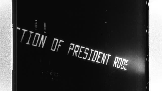 A jubilant crowd cheers as an electric billboard advises that U S President Franklin D Roosevelt has been elected to to a third term