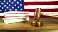Judge banging gavel.  American flag backdrop.