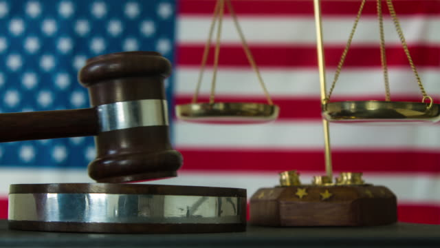 Judge calling order with hammer and gavel in american court with flag background