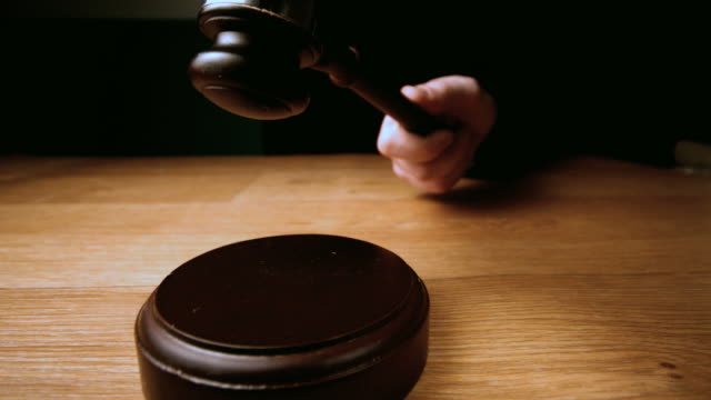 Judge hammering gavel onto sounding block