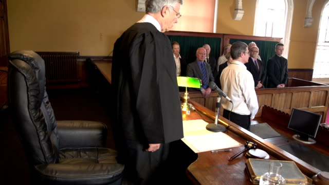 Judge walking into Court, with Jury Standing in Courthouse