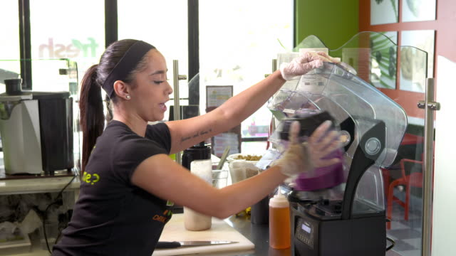 MS juice bar girl removes plastic jar from blender and pours raw pitaya smoothie into plastic serving cup