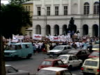 July 12 1989 ZO Crowd at Presidential Palace standing and holding banners for Solidarity traffic moving on street / Warsaw Poland