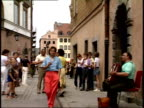 July 14 1989 ZO Accordionist in Old Town playing and singing on sidewalk with crowds walking around narrow streets tipping accordionist / Warsaw...