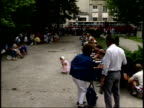 July 14 1989 MONTAGE Pedestrians standing behind gate while others inside gated treelined park sitting and writing notes / Warsaw Poland