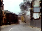 July 23 1972 WS ZO City street as IRA bomb goes off on Bloody Friday/ WS People walking through debrisstrewn street/ WS PAN Man running across...