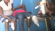 July 7 2010 MS Group of young amputees sitting on bench with prosthetic legs / PortauPrince Haiti