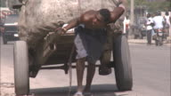 July 7 2010 TS Laborer hauling rickshaw loaded with huge bundles of goods / PortauPrince Haiti