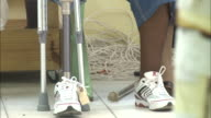 July 7 2010 MONTAGE Earthquake survivor sitting in waiting room wearing prosthesis and doctors tending to patients in treatment room / PortauPrince...