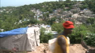 July 7 2010 MONTAGE Villagers walking along a steep path near makeshift shelters a Red Cross aid tent and a worker scooping rubble into a sack / Haiti