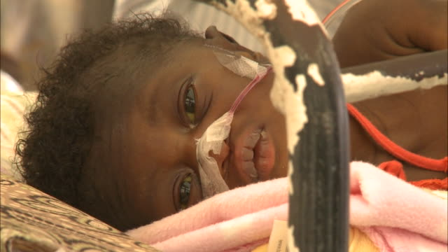 July 7 2010 MONTAGE Young earthquake survivor in hospital cribs wearing nasal cannula / PortauPrince Haiti