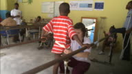 July 7 2010 ZI Physical therapist helping fit young amputee's prosthetic leg and patient practicing walking during orthopedic therapy / PortauPrince...