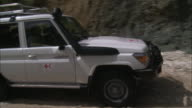 July 7 2010 TS Red Cross Jeep driving down a rocky dirt road next to embankment as villagers look on / Haiti