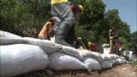 July 7 2010 LA Workers wearing rubber boots gloves and hard hats digging with pickaxes and filling sacks with rubble / Haiti