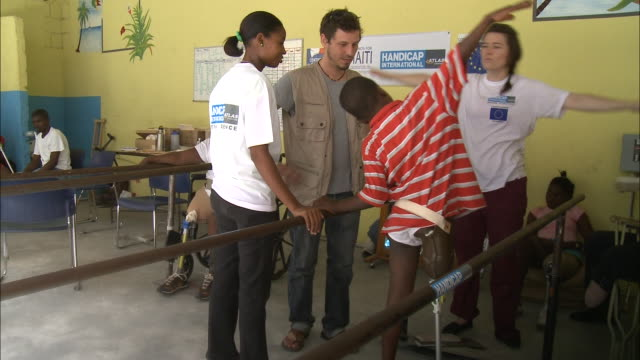 July 7 2010 WS Young amputee exercising arms during orthopedic therapy with physical therapists adjusting prosthetic leg / PortauPrince Haiti