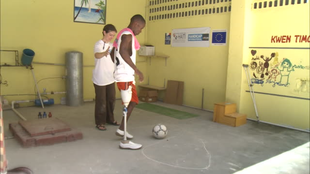 July 7 2010 WS Young amputee with prosthetic leg kicking soccer ball during physical therapy / PortauPrince Haiti