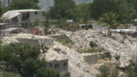 July 9 2010 MONTAGE Locals walking through ruins of destroyed buildings / Haiti