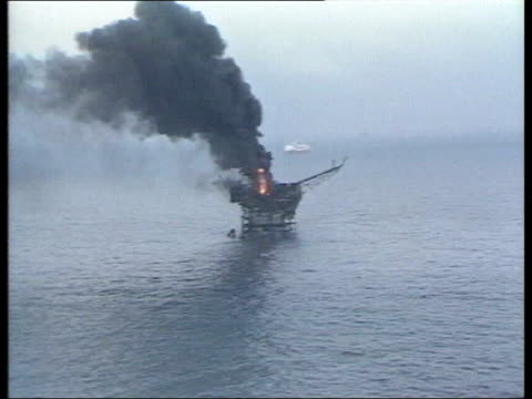 July In 1988 Piper Alpha oil rig exploded EXT Black column of smoke rising from burning oil rig / INT Pilot ZOOM IN burning rig