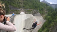 BASE jumper descends from high concrete dam to valley below