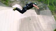 BASE jumper plunges down concrete dam face