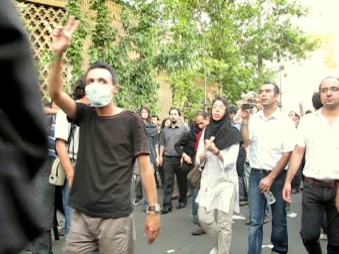 28 Jun 2009 MS Demonstrators walking on sidewalk making peace signs / Teheran Iran / AUDIO