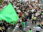 10 Jun 2009 WS HA Man spinning with large green flag amongst demonstrators on city square / Teheran Iran / AUDIO