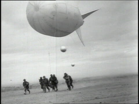 June 1944 TS Group of soldiers running across an airfield maneuvering a barrage balloon into position / France