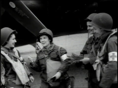 June 1944 WS Group of women medical transport pilots standing around and talking waiting near their aircraft / France